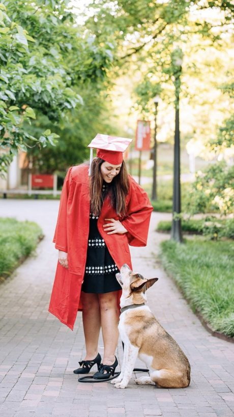 Brittany Wall in red cap and gown with a dog