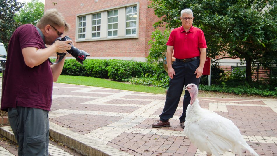 a photographer and a man outside with a white turkey hen
