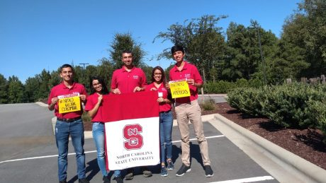 Oviedo lab visiting students holding an NC State banner