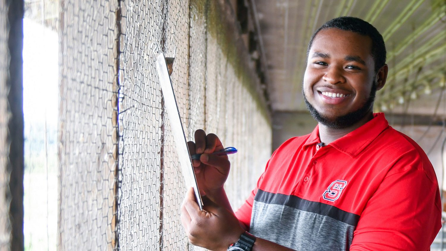 A young Black man in a poultry house wearing an NC State shirt.