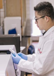 A man, Sean Chen, in a lab, wearing a lab coat and blue gloves