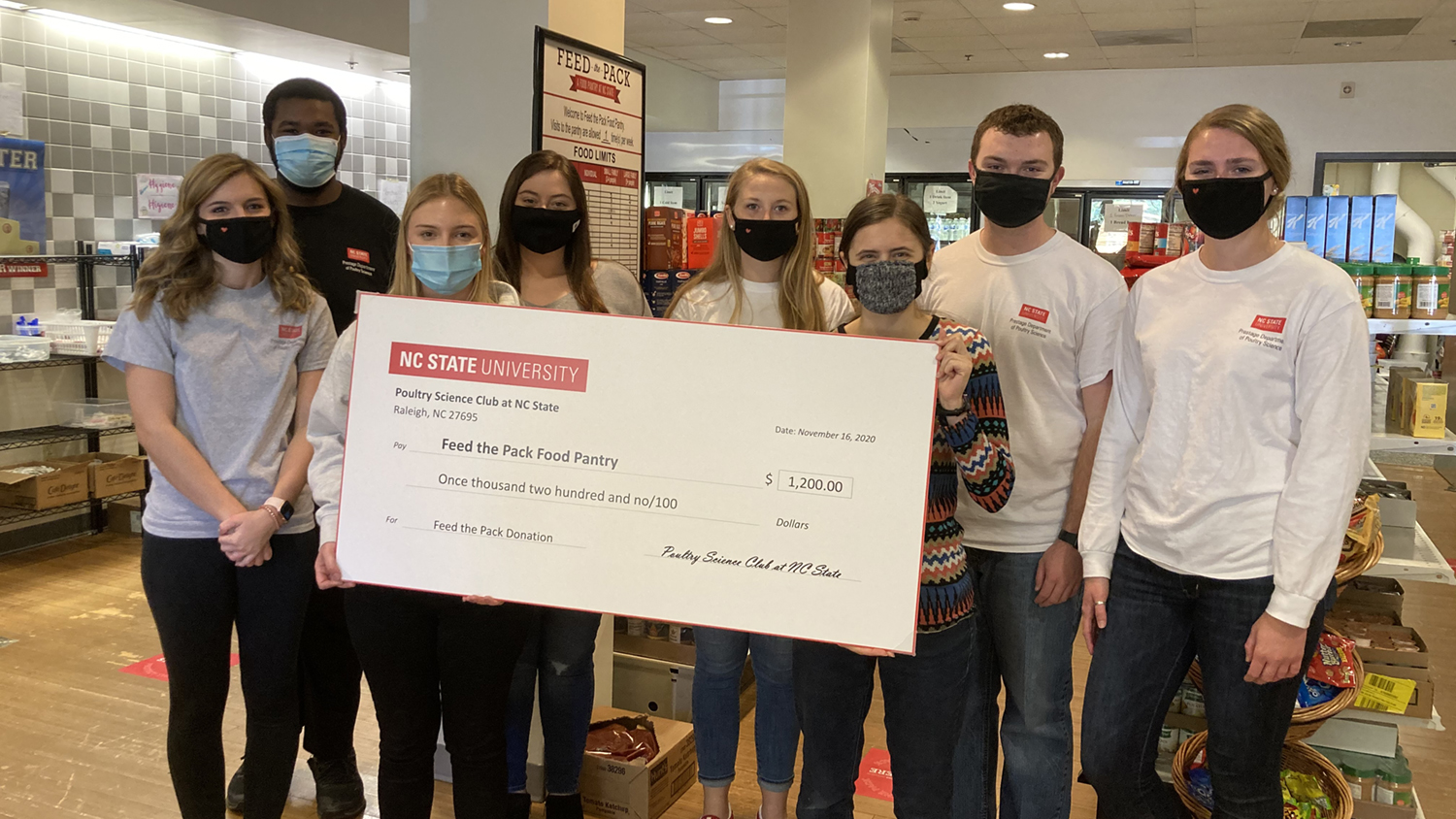 students in masks hold a large check