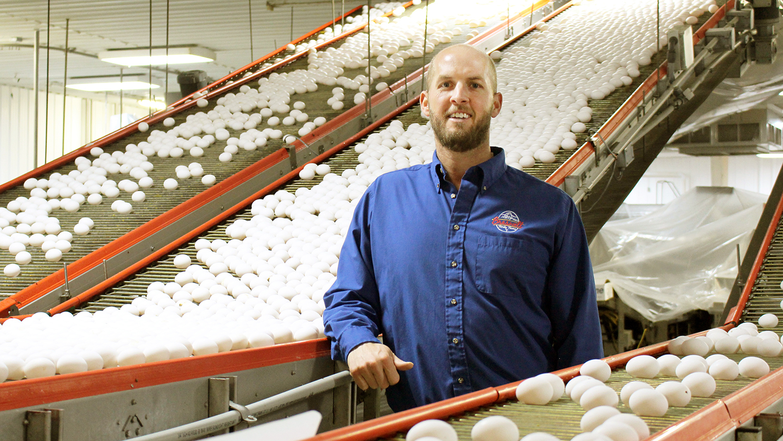 Man standing in an egg factory