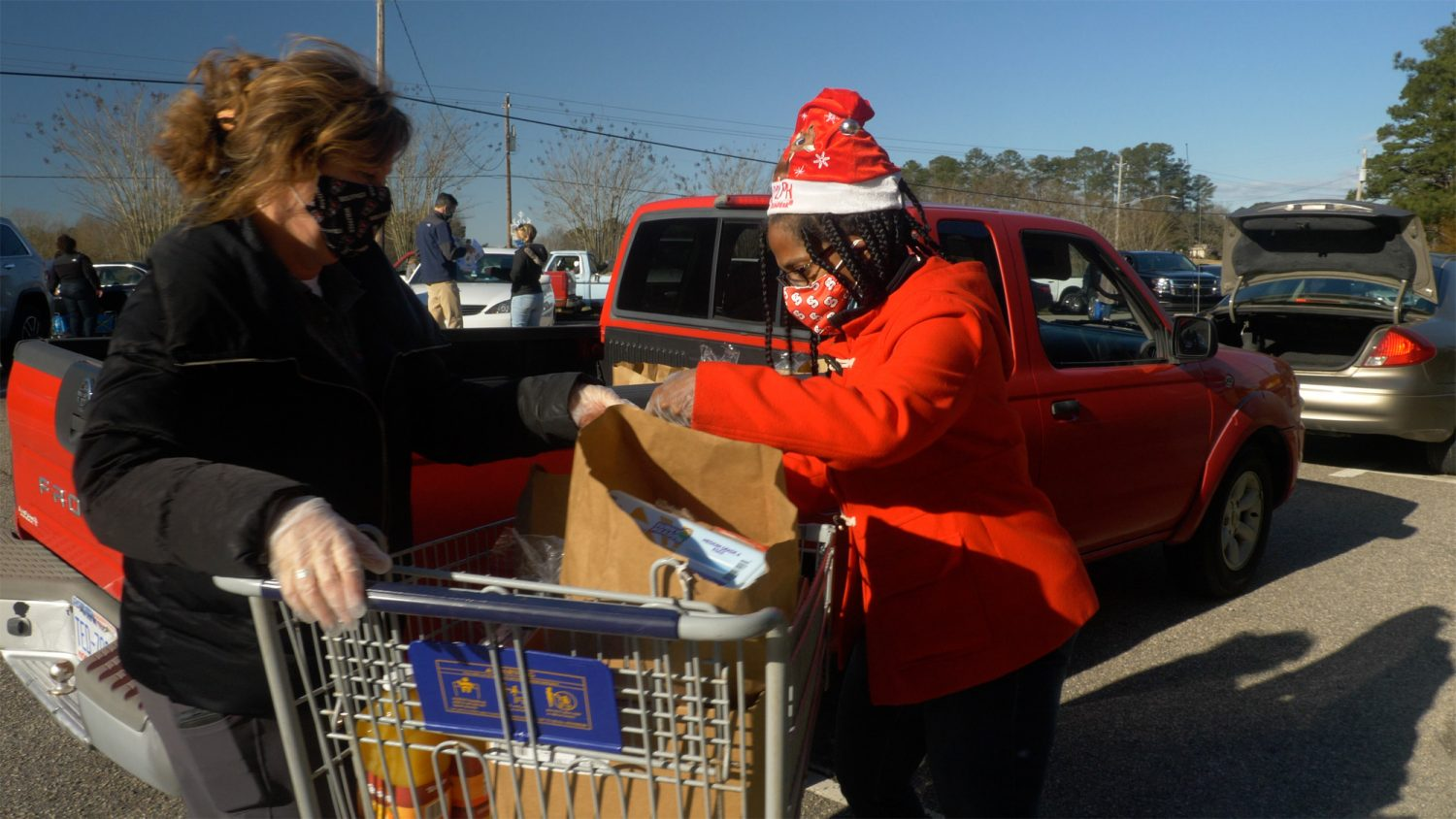 Two women assist with loading grocery bags into the back of a pickup truck as part of N.C. Cooperative Extension's Wake County Center food drive during the COVID-19 pandemic.