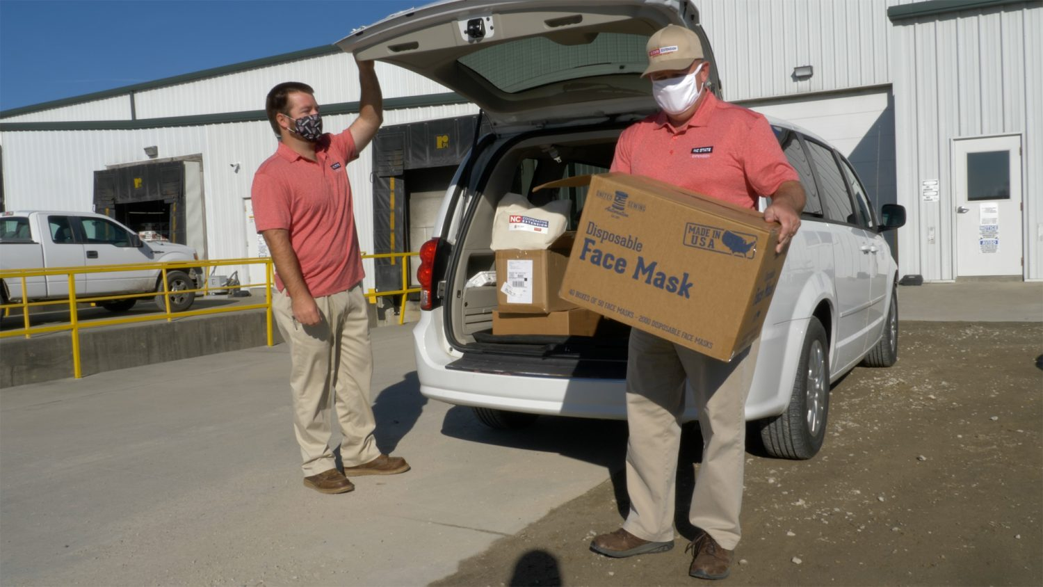 N.C. Cooperative Extension employees unload face masks from the trunk of a van during the COVID-19 pandemic.