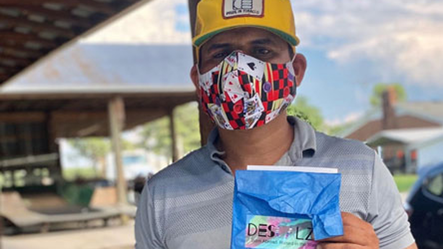 A farmworker wearing a face mask holds up a face mask package.