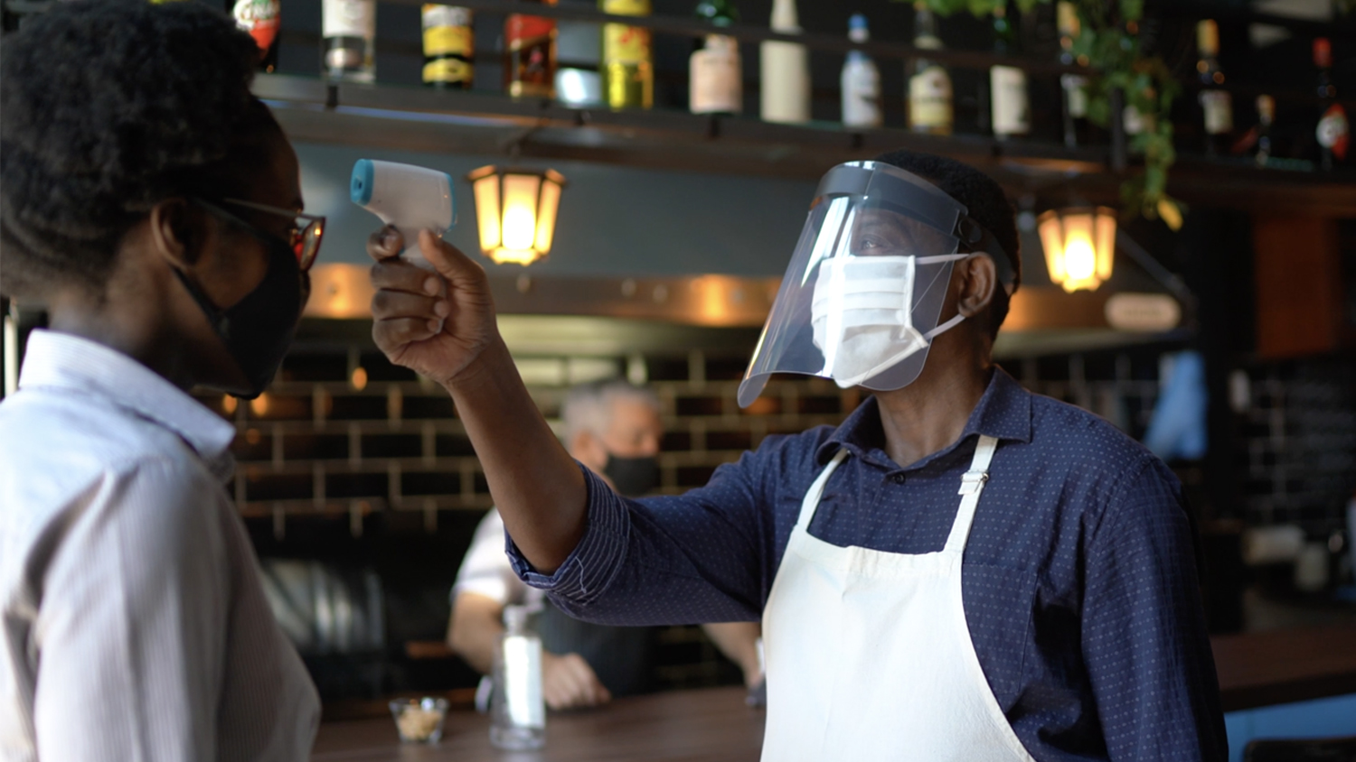 A restaurant employee wearing a face shield uses a digital thermometer to take the temperature of a guest when entering the restaurant.