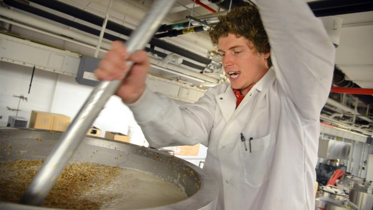 An NC State brewer working in the brewery.