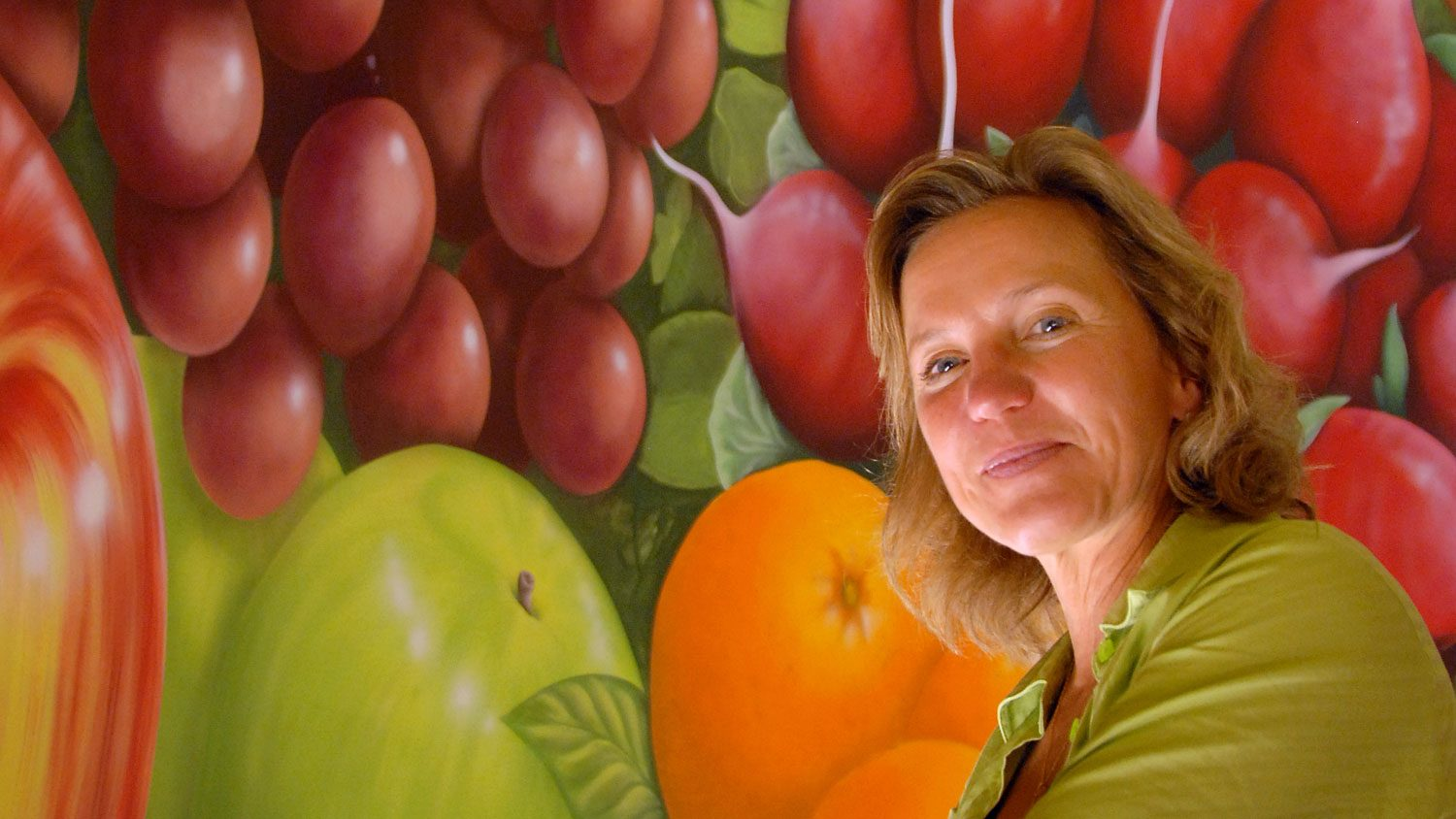 Woman in front of fruit mural