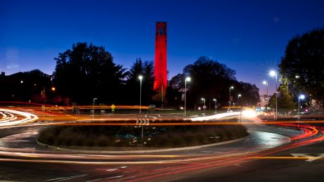 NC State Bell Tower at night with traffic passing through a roundabout in the foreground.