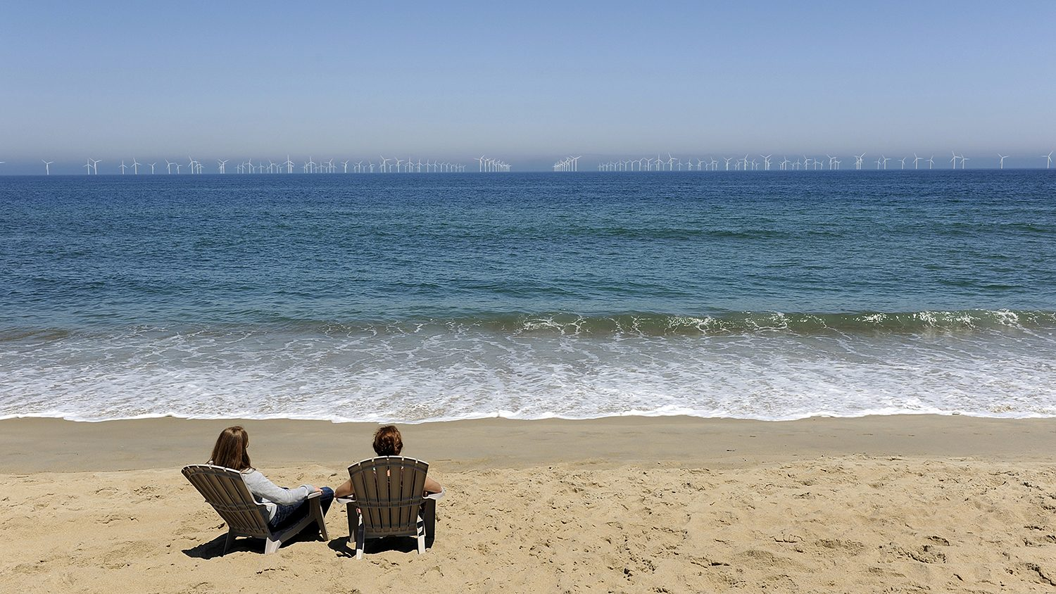 Two people on beach with wind farm in the distance.