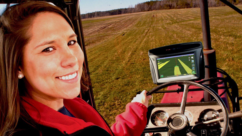 Female farmer driving a tractor in a field.