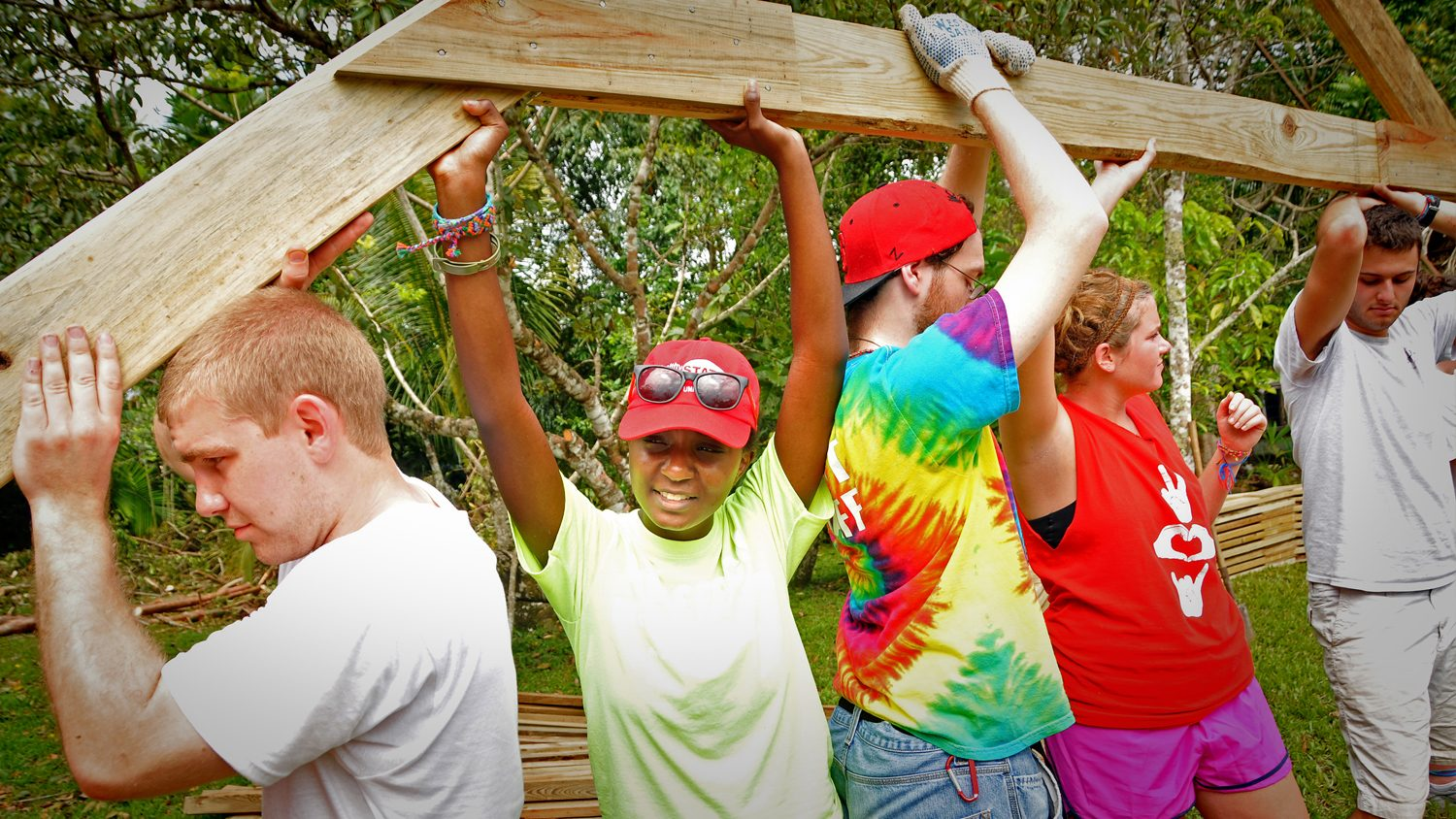 Diverse students building a house
