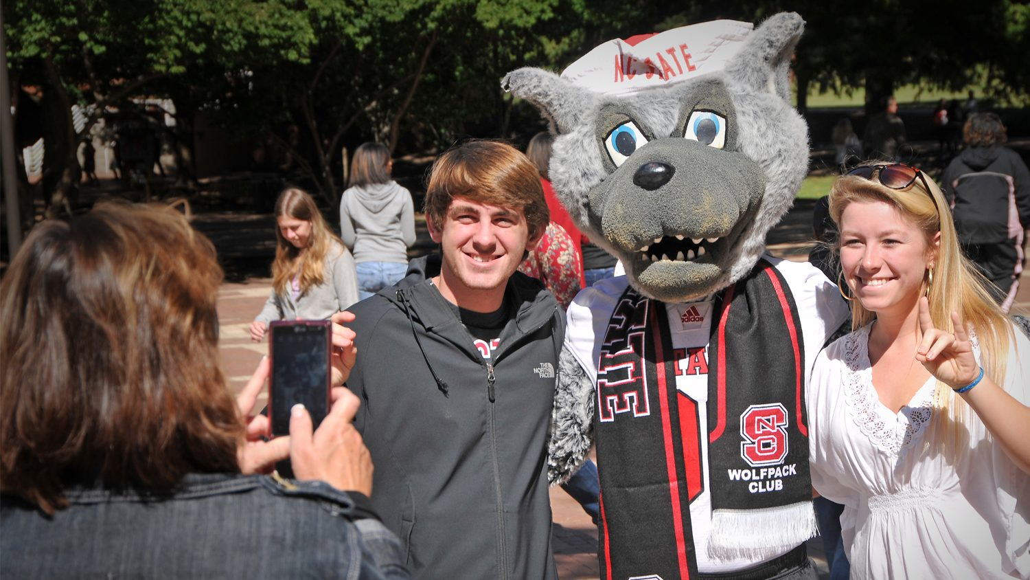 NC State students pose for a photo with college mascot Mr. Wuf.