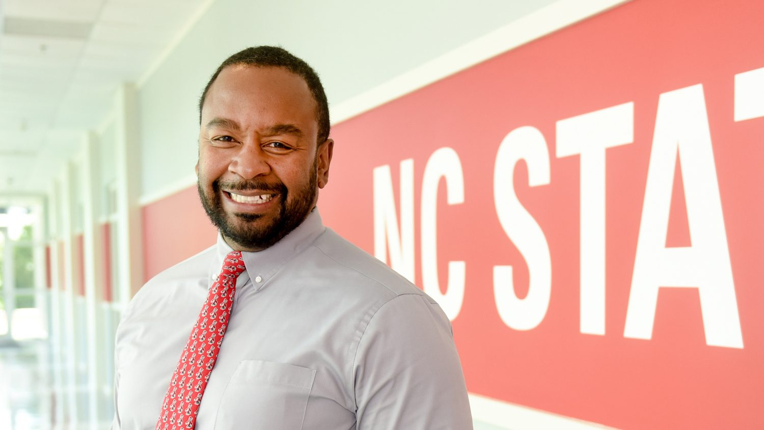 North Carolina Cooperative Extension Service Associate Director Travis Burke poses for a headshot in front of the NC State University logo.