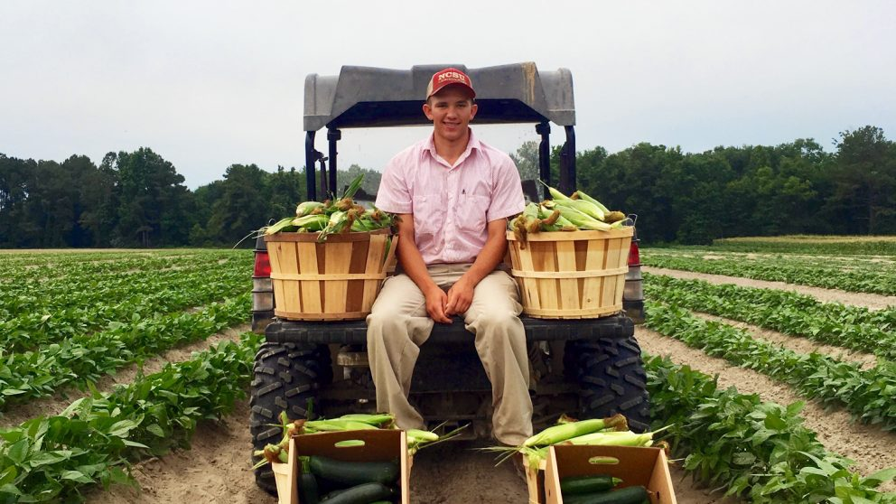 NC State College of Agriculture and LIfe Sciences student Collin Blalock sits on the back of a tractor with in a field. He is surrounded by bushels of produce.