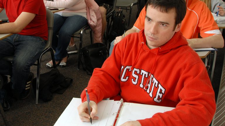 An NC State student sitting at a desk in a classroom.