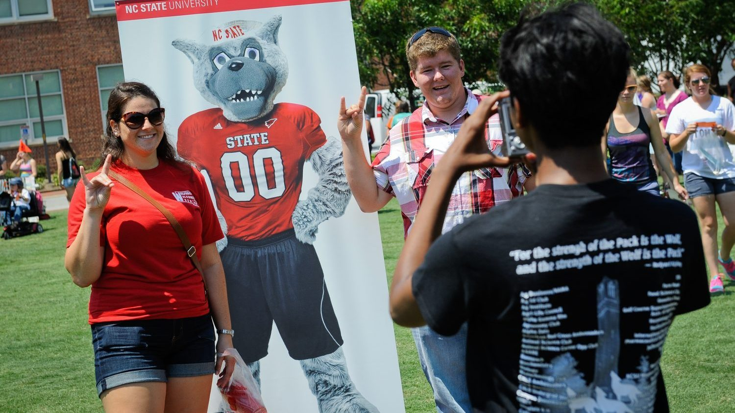 Students pose with a poster of Mr. Wuf at the CALS college connection event at NC State University.