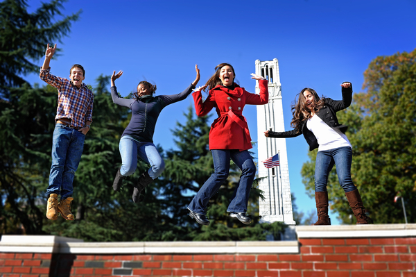 Students in front of the belltower at the entrance to NC State on Hillsborough Street. Photo by Marc Hall