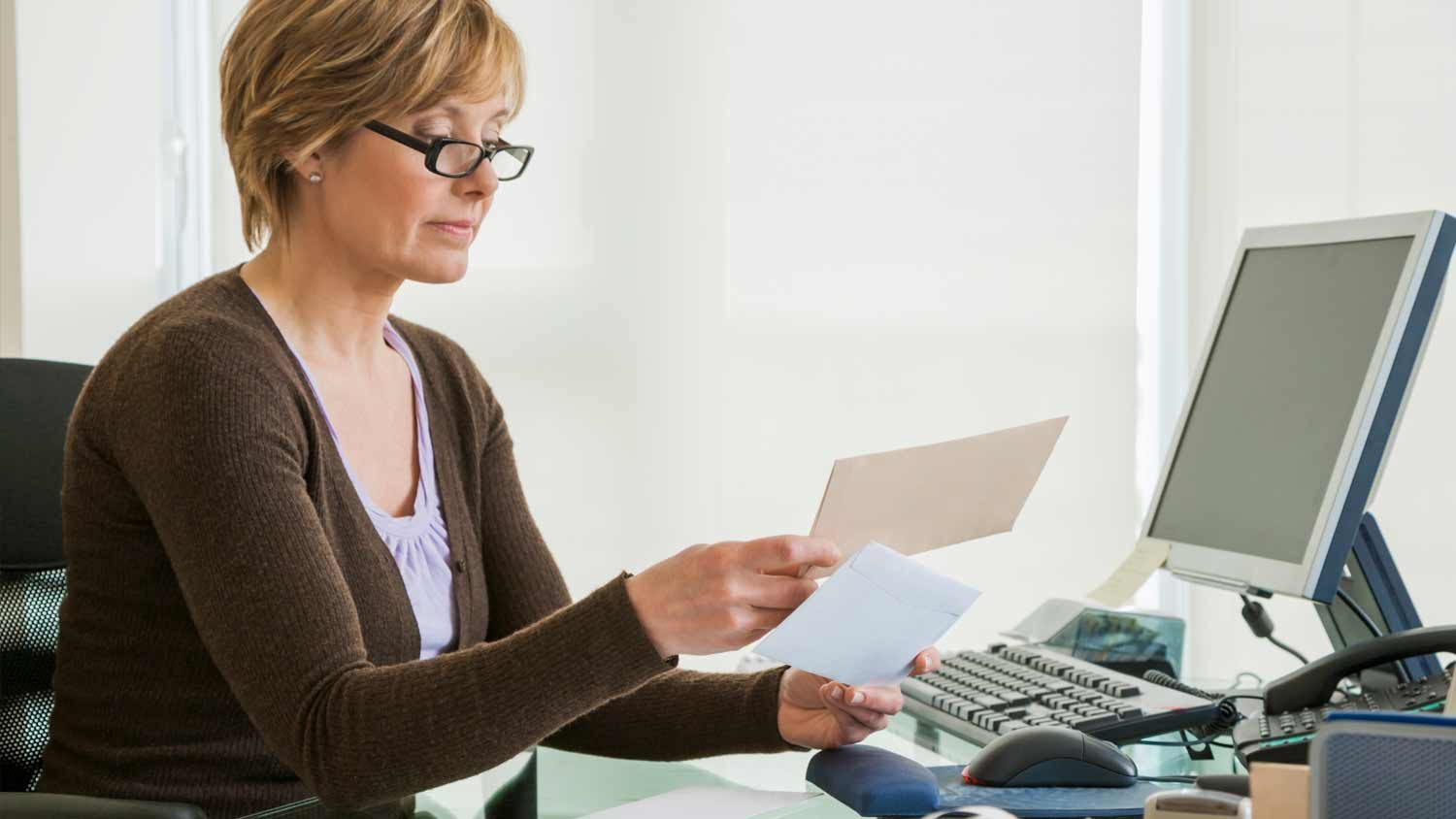 Woman sitting at desk looking at envelopes