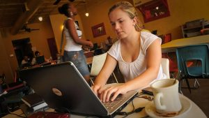 Woman making donation to CALS online while at local coffeshop.
