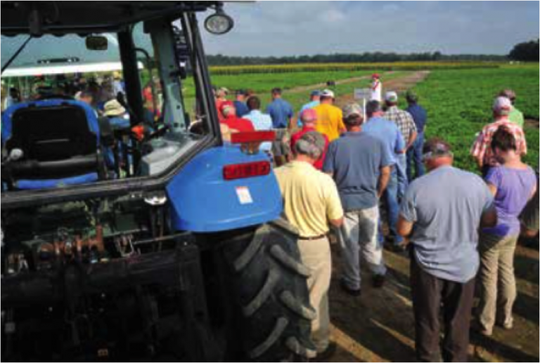 A group gathered in a field with a trackgor in the foreground at a Nickels for Know-How Extension Event