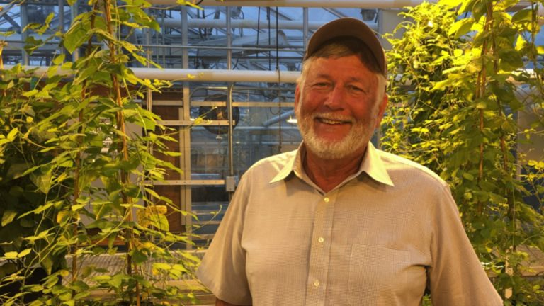 Tommy Carter, smiling, in a campus greenhouse.
