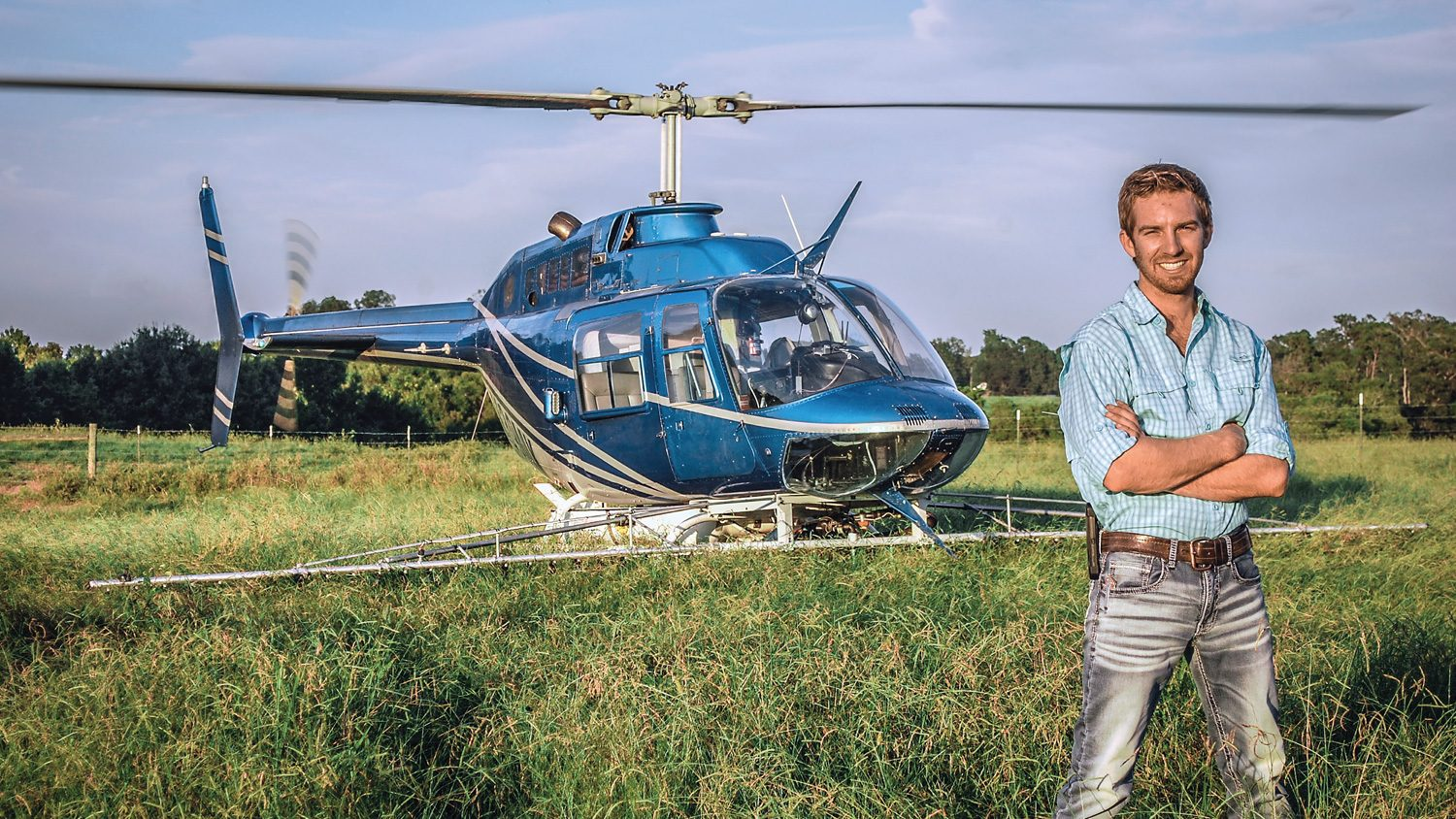 CALS Agricultural Institute graduate Jacob Tarlton in a field with his helicopter.