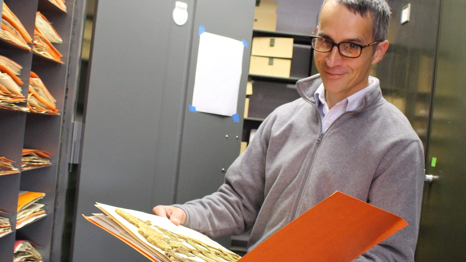 Dr. Alexander Krings holds a folder containing one of the Vascular Plant Herbarium's plant specimens.