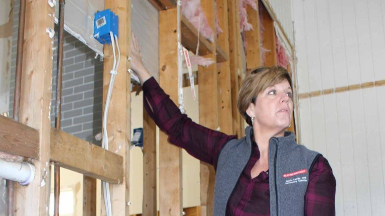 Sarah Kirby pointing to drywall behind exposed wooden studs in a flooded home.