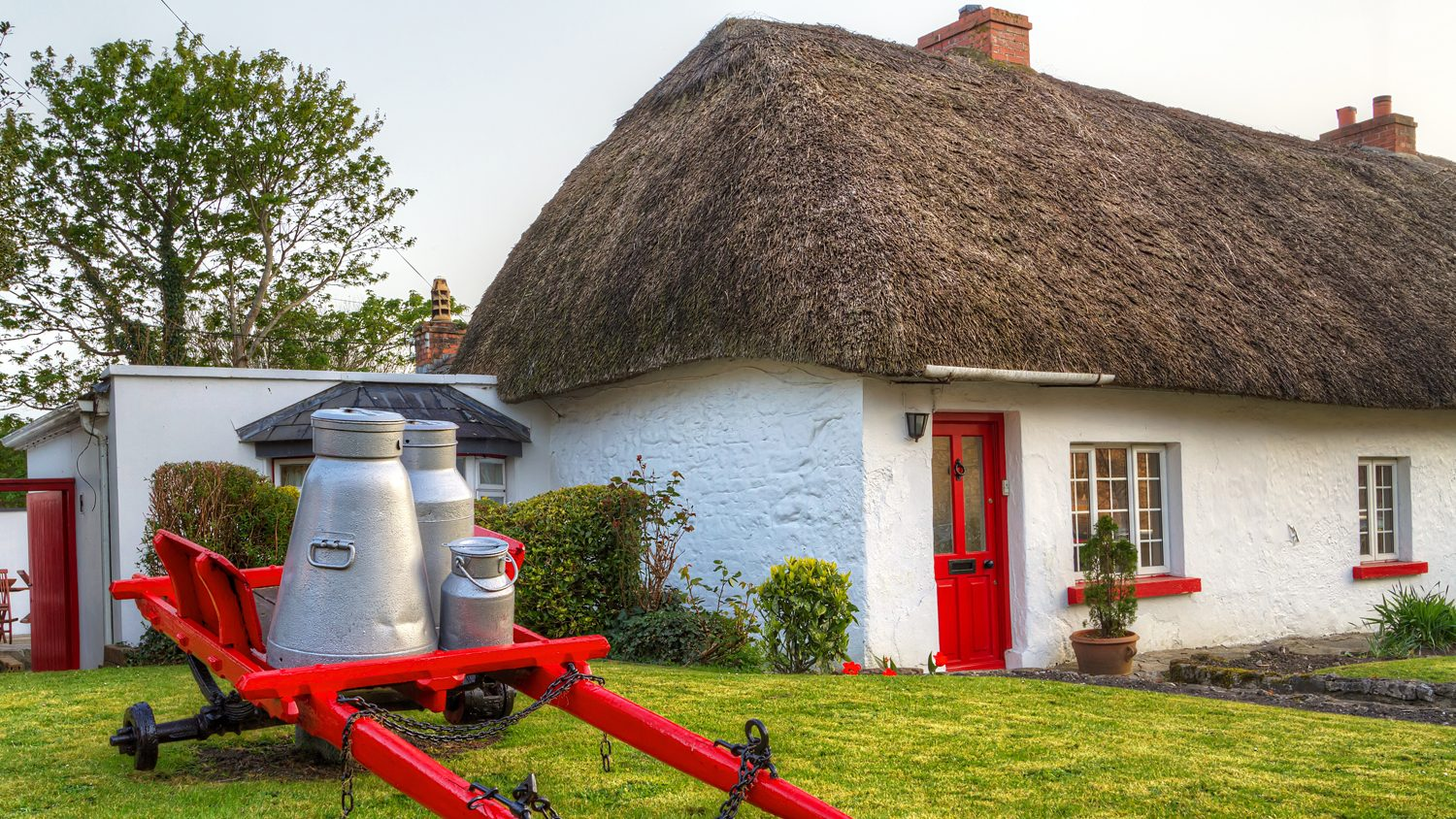 Thached-roof farm cottage in Ireland with milk cart in front lawn.