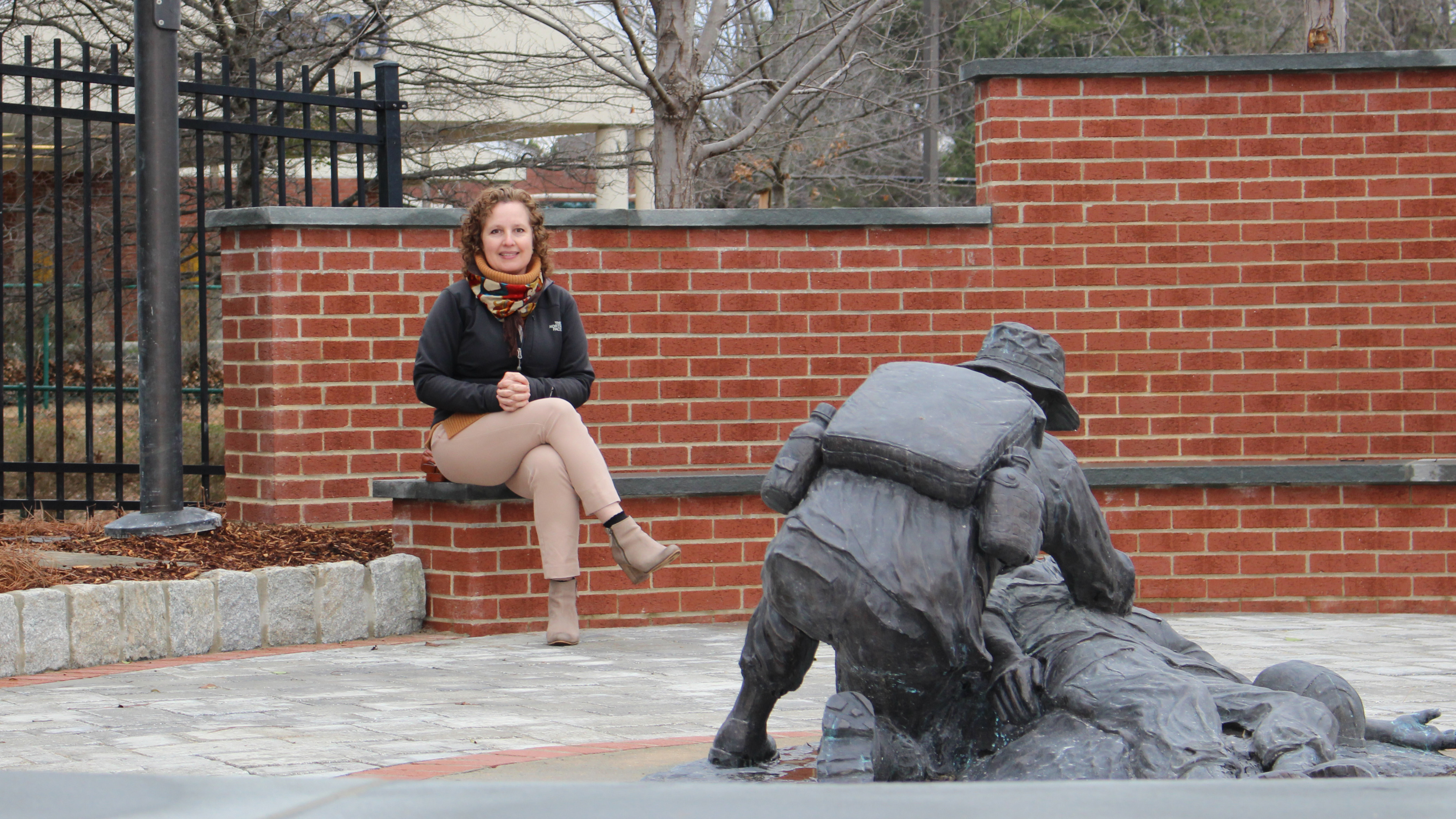 Julieta Sherk seated in a patio. In the foreground: a statue of a medic aiding a wounded soldier.