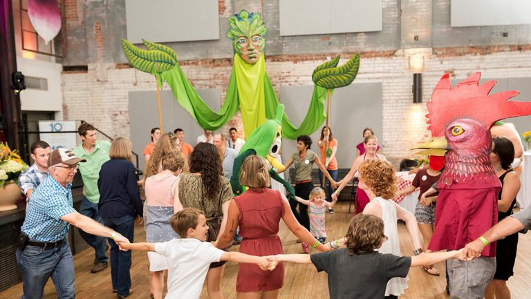 Multiple generations join hands, dancing around large puppets