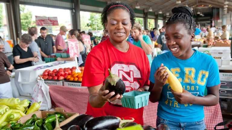 A woman and her daughter peruse produce at the Farmers Market.