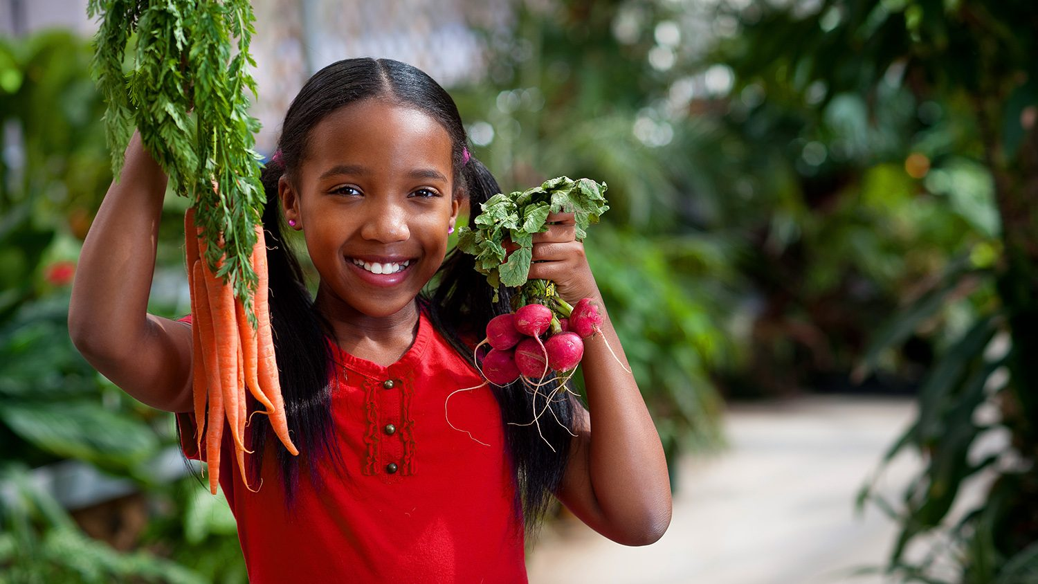 girl holding carrots and radishes
