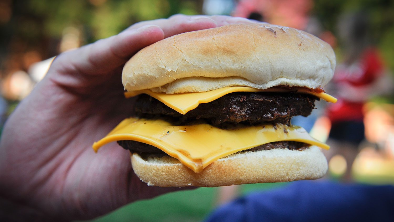a hand holding a cheeseburger