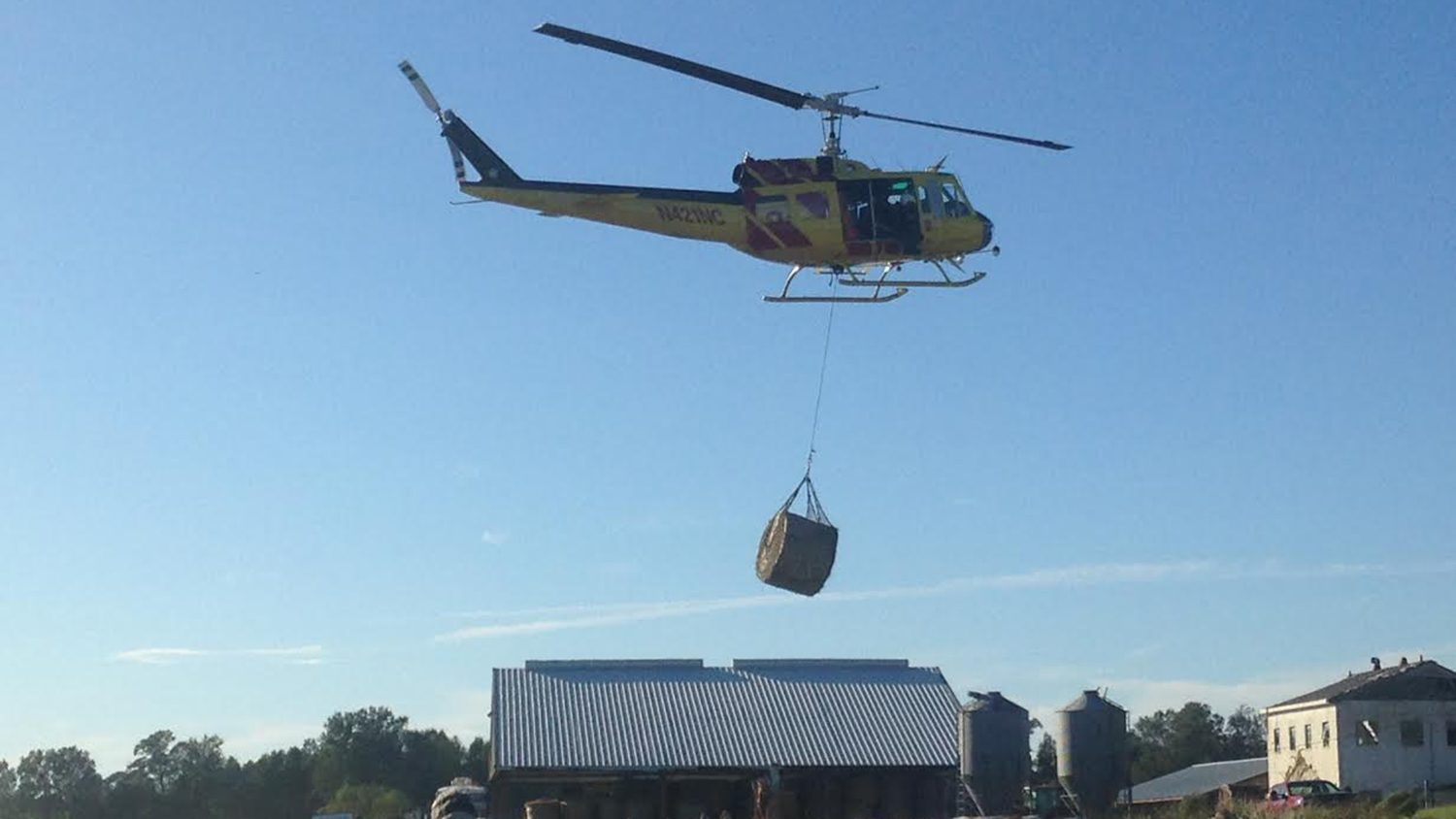 Helicopter lifting hay bale to animals on Cherry Research Farm in wake of Hurricane Matthew.