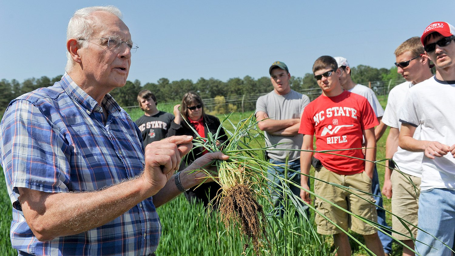 Bob Patterson with students outside in an agricultural field.