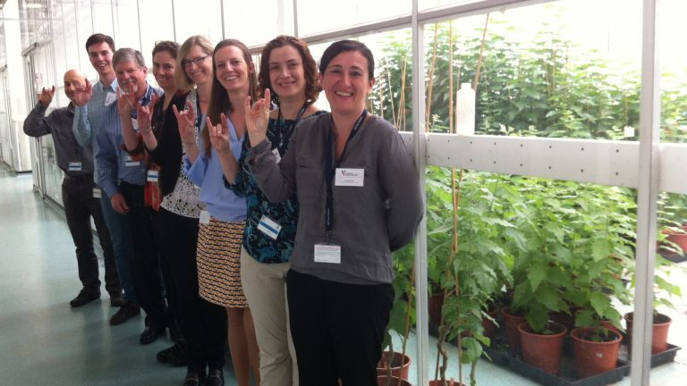 Group of scientists standing outside a greenhouse.