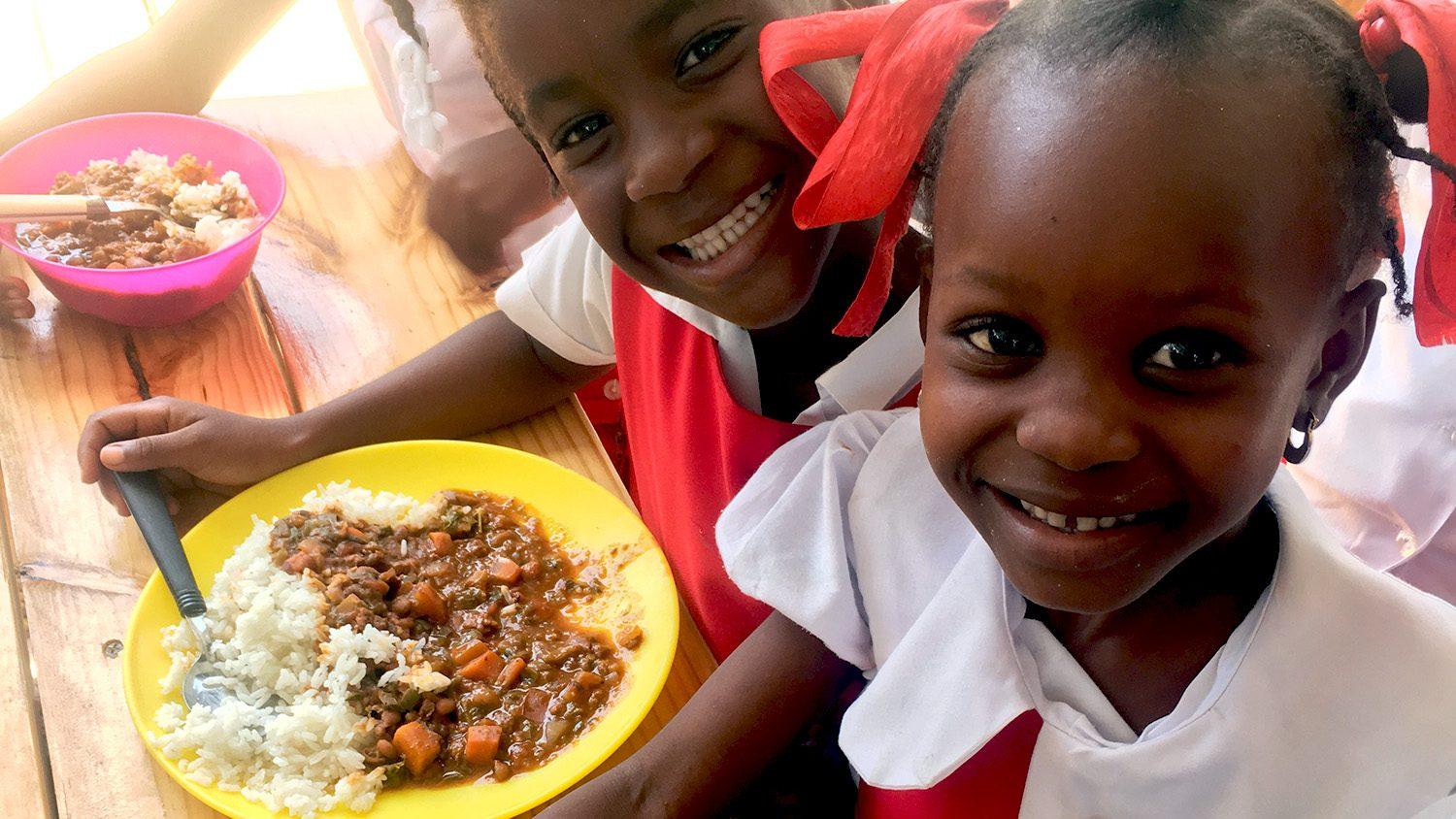 Haitian children eating lunch via the NCSU Haiti Goat Project