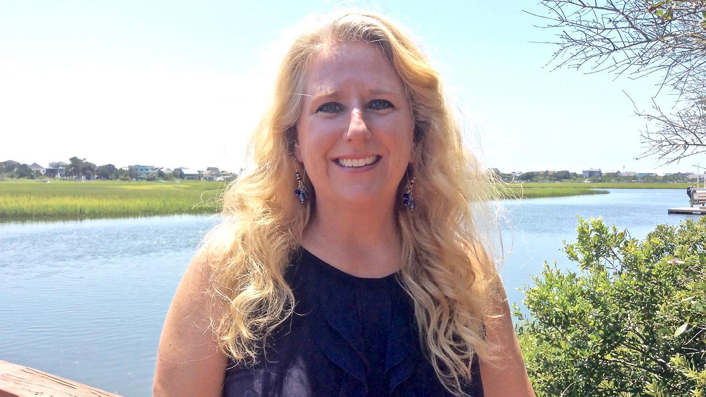 CALS alumna Stephanie Jones standing on a bridge by a lake