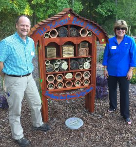 In the Choice Plants garden, Marshall Warren and Jody Boronkay standing at a wooden structure known as the bee hotel.