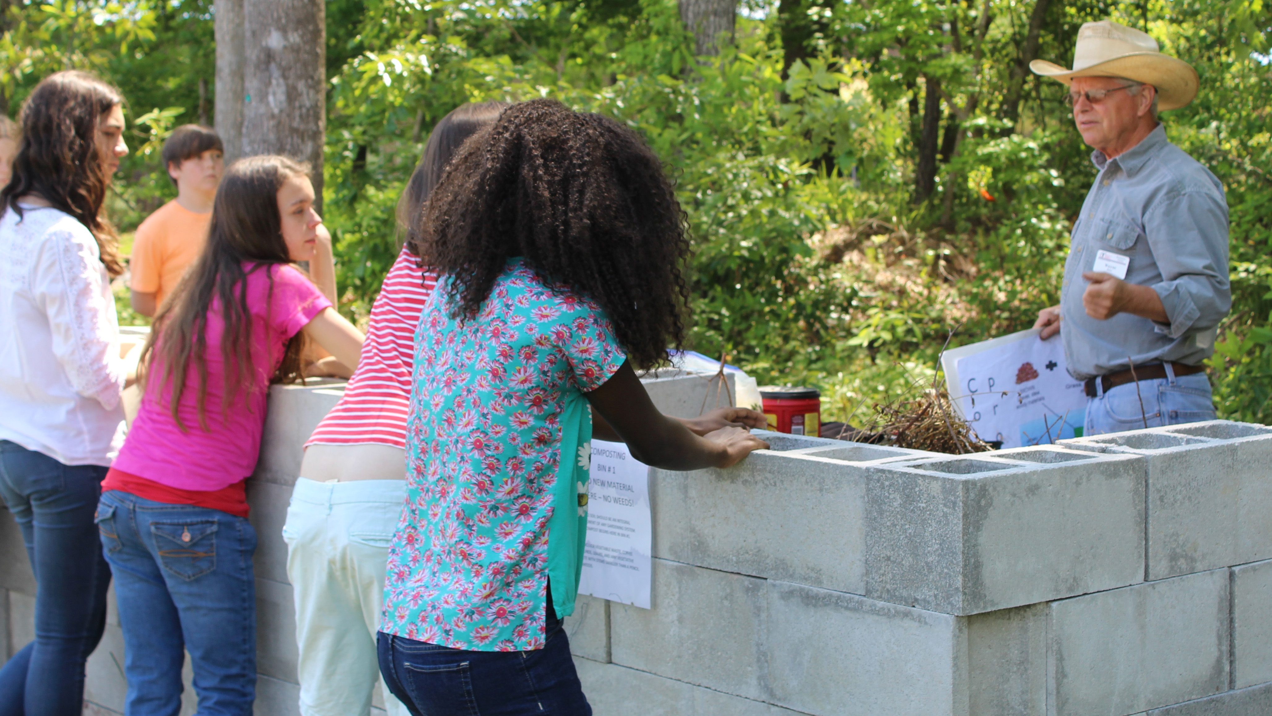 Students learn about composting from a Master Gardener volunteer.
