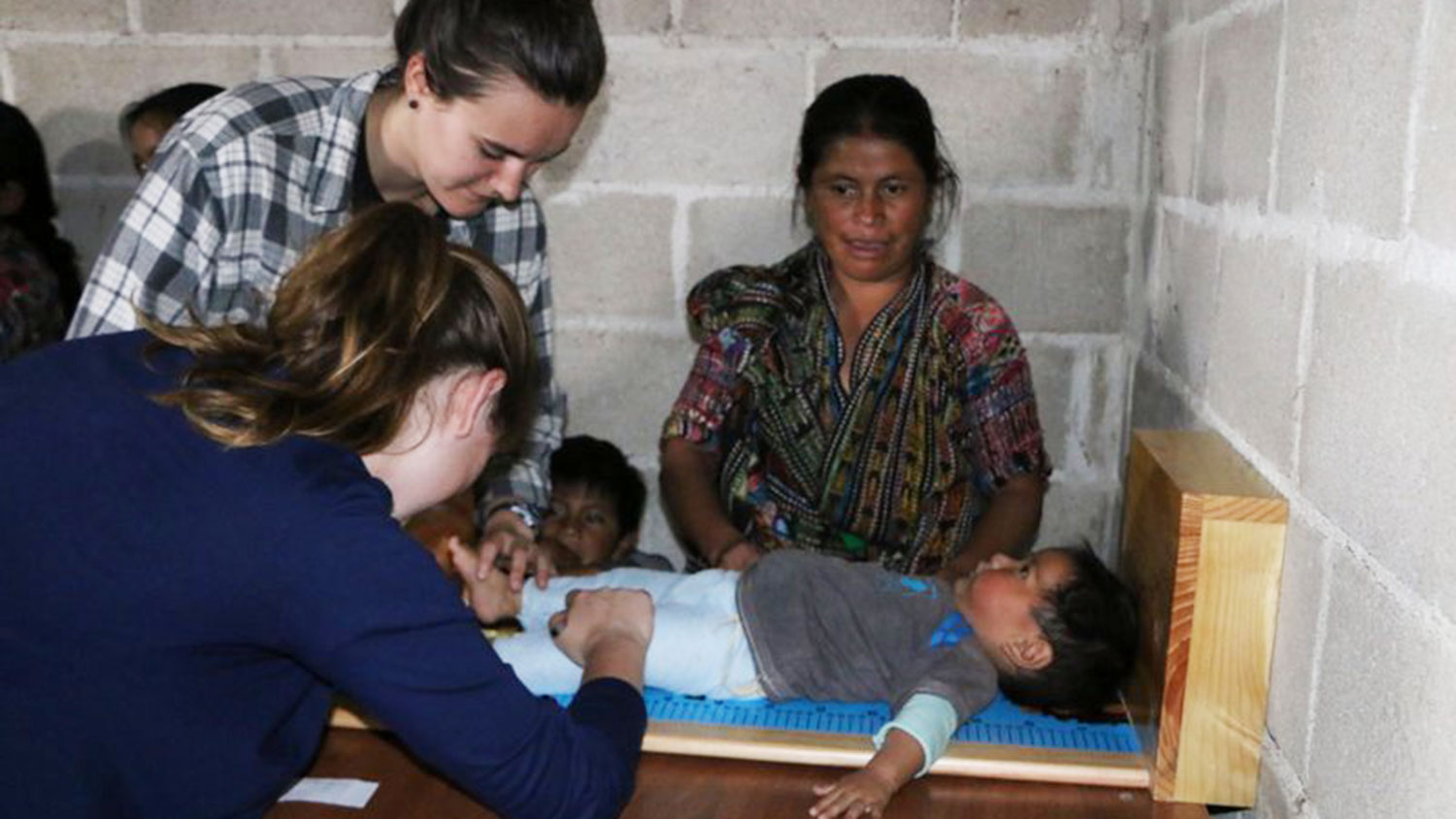 CALS student Kati Scruggs assisting with a child's medical exam in Guatemala