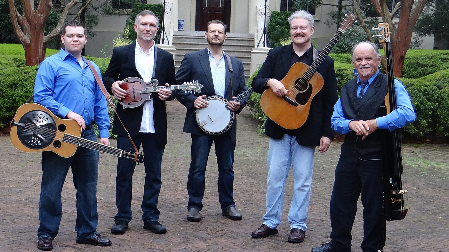 Four men standing outside and holding bluegrass instruments.