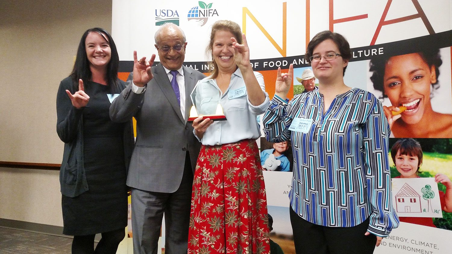 Celebrating Wolfpack-style at the NIFA awards ceremony were (left to right): Rebecca Goulter, NoroCORE assistant director; Sonny Ramaswamy, NIFA director; Lee-Ann Jaykus, NoroCORE director; and Elizabeth Bradshaw, NoroCORE communications director.