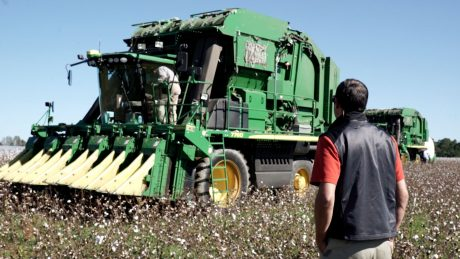 CALS alum Donny Lassiter standing in a field with a large piece of agricultural equipment