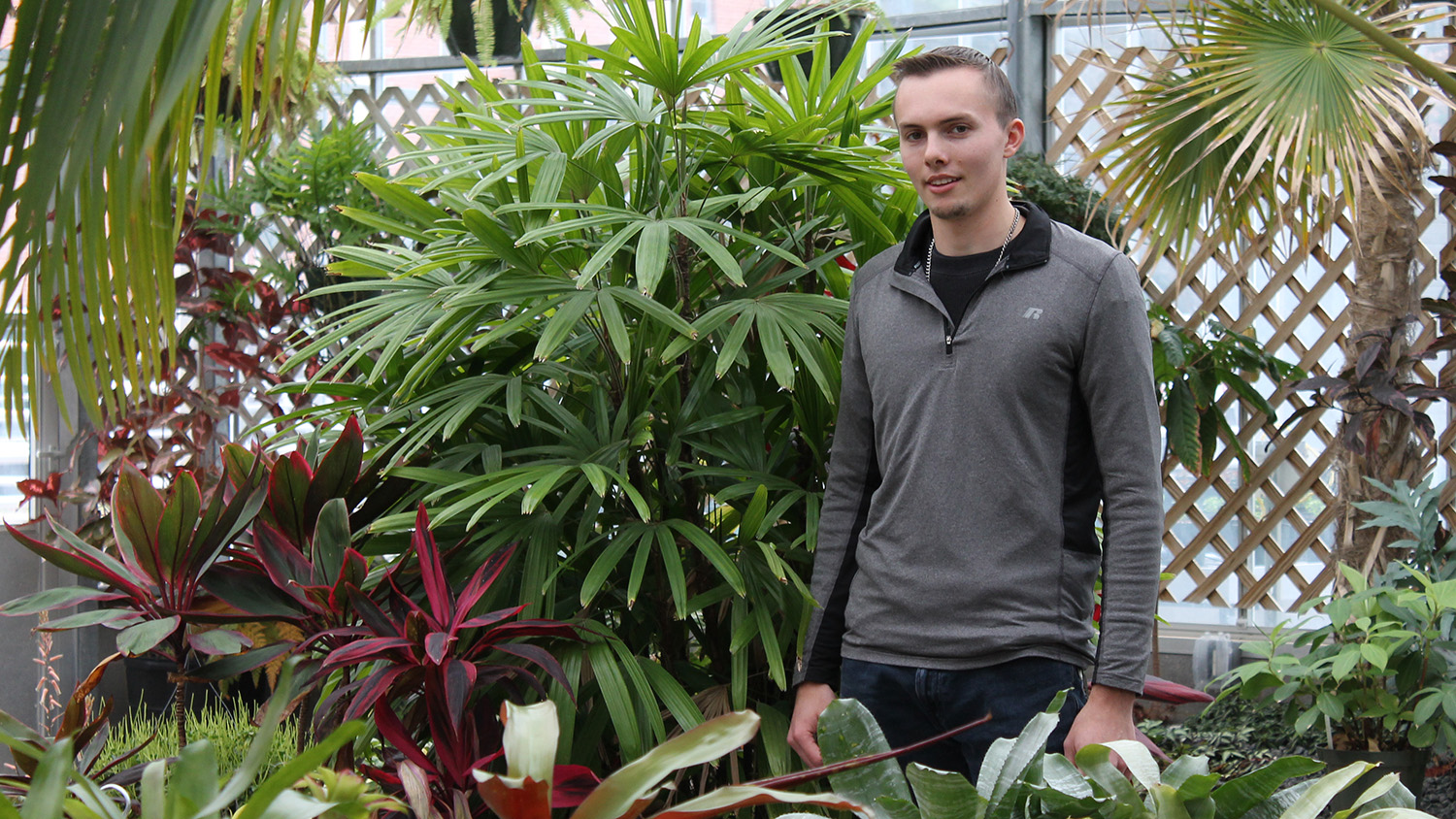Student surrounded by tropical plants