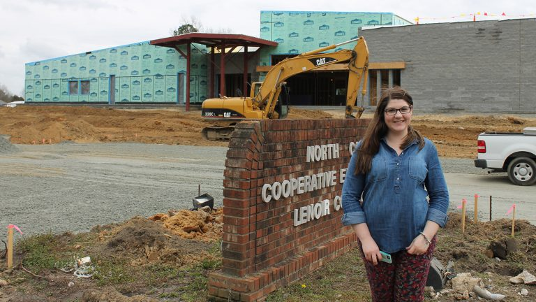 Woman behind North Carolina Cooperative Extension Lenoir County sign, at the construction site for the new county center.