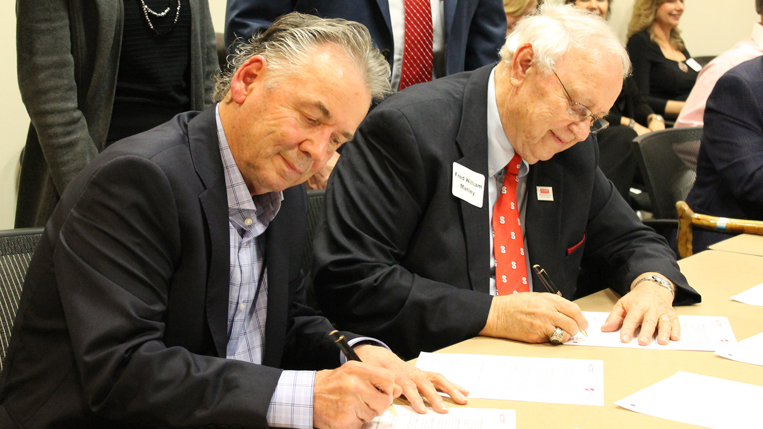 Two men seated at a table, signing papers.